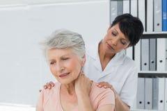 看充满脖子痛的按摩医生资深妇女 免版税库存图片