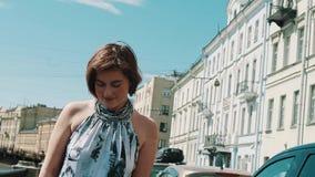 看入照相机的被察觉的礼服的快乐的女孩堤防在老城市 股票录像