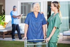 看其中每一的微笑的残疾妇女和护士 库存照片