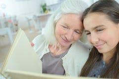看册页的妇女和孙女 免版税图库摄影