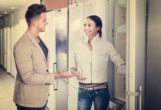 看冰箱的愉快的年轻家庭在商店 库存图片