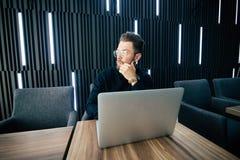 看去,当坐有膝上型计算机和其他项目的时办公桌的衣服的可爱的年轻有胡子的人 免版税库存图片
