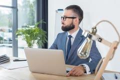 看去,当坐有膝上型计算机的时工作场所的周道的商人 免版税库存图片