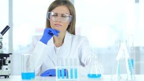 看反应的女性科学家发生在烧瓶在实验室 股票视频