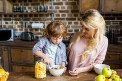 看可爱的矮小的儿子的微笑的年轻母亲准备玉米片 免版税库存图片