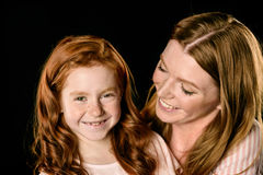 看可爱的红头发人女儿的微笑的母亲画象 库存照片
