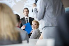 看同事的微笑的女实业家讲话在研讨会期间 免版税库存照片