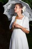 看向上在一件白色礼服和与鞋带伞的妇女 免版税库存照片