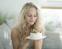 看吸引的蛋糕的美丽的少妇在房子里 免版税图库摄影