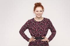 看和微笑与happ的照相机的可爱的红头发人妇女 库存照片