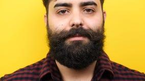 看和微笑对照相机的年轻有胡子的行家 影视素材