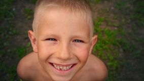 看和微笑直接地照相机,六岁小孩的贯穿的神色的一个蓝眼睛的小男孩的特写镜头画象 影视素材