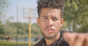 看和指向与他的手指的年轻英俊的非裔美国人的男性篮球运动员特写镜头画象  股票视频