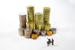 看和指向堆的微型商人在白色背景的硬币为事务,经济概念 免版税库存照片