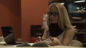 看和翻转日志书的美丽的妇女在背景笔记本的桌 影视素材