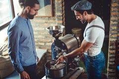 看咖啡烘烤器机器的男性所有者 免版税图库摄影