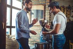 看咖啡豆的男性所有者由咖啡烘烤器 免版税库存照片