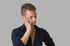 看哀伤,沮丧的白肤金发的年轻的人下来 免版税库存图片