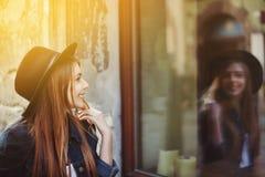 看商店窗口的年轻微笑的妇女画象  式样佩带的时髦的宽充满的黑帽会议 背景秀丽城市生活方式都市妇女年轻人 免版税库存照片