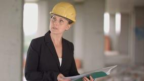 看图纸的女性建筑师建造场所 免版税图库摄影