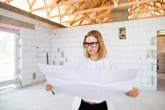 看图纸的建造场所的建筑师 免版税图库摄影