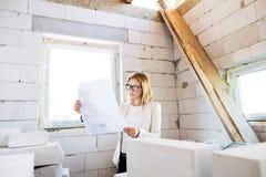看图纸的建造场所的建筑师 免版税库存照片