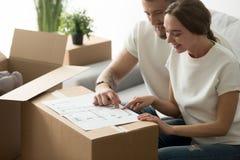 看图纸的愉快的年轻夫妇计划新的家庭设计 免版税图库摄影