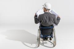 看图纸的轮椅的残疾建筑师 图库摄影
