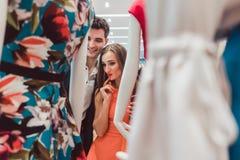 看在一个时装模特的妇女和人礼服在时尚商店 免版税库存照片
