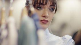 看在一个机架的年轻可爱的俏丽的失望的妇女接近的射击衣裳在服装店 股票视频