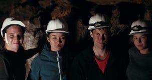 看在一个黑暗的洞的年轻朋友探险家照相机 股票录像