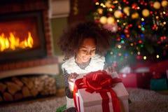 看在不可思议的礼物的惊奇的小女孩 库存照片