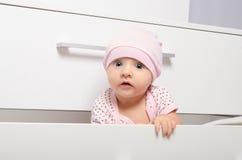 看在五斗橱的好奇婴孩外面 库存图片