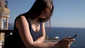 看在从一个豪华大阳台的海的少女 享用天空蔚蓝的妇女停留在阳台 股票录像