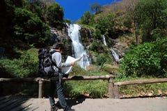 看在他的手上的年轻亚裔背包徒步旅行者地图在瀑布国家公园 库存图片