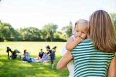 看在公园的母亲运载的女儿 免版税库存照片