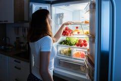 看在冰箱的妇女食物 库存照片