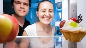 看在冰箱里面的微笑的年轻家庭特写镜头画象  免版税库存照片