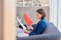看在办公室长沙发的严肃的女实业家文书工作 免版税库存照片