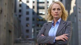 看在办公楼背景的年迈的母上司照相机折叠的胳膊 股票录像
