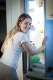 看在厨房的冰箱里面的美丽的妇女ni 库存照片