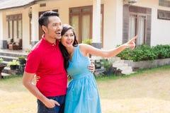 看在同一个方向的快乐的年轻夫妇在前面 免版税库存照片