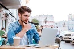 看在咖啡馆的沉思年轻偶然人膝上型计算机户外 库存图片