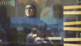 看在咖啡馆的窗口的hijab的妇女,自由的回教女性,通信 股票视频