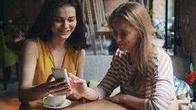 看在咖啡馆谈的笑的快乐的朋友智能手机屏幕获得乐趣 股票录像