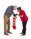 看在圣诞节长袜的好奇夫妇 免版税库存图片