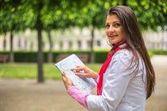 看在地图的少妇城市公园巴黎,法国 库存照片