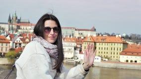 看在城市堤防的中景微笑的典雅的女性旅游挥动的手照相机身分 影视素材