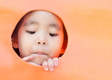 看在塑料孔外面的亚裔女孩 图库摄影