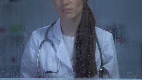 看在多雨窗口的不快乐的女性医生在耐心死亡,消沉以后 影视素材